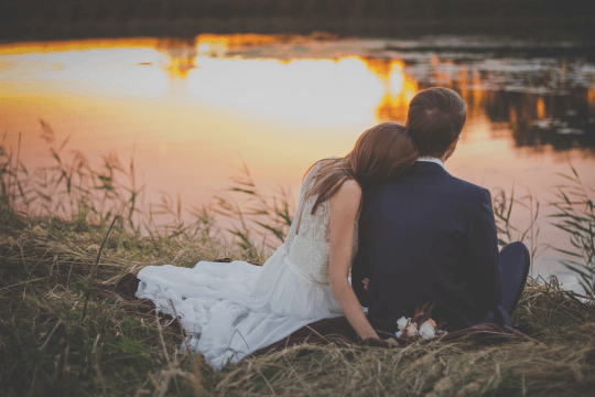 Married couple in front of a lake contemplating, prenuptial agreement