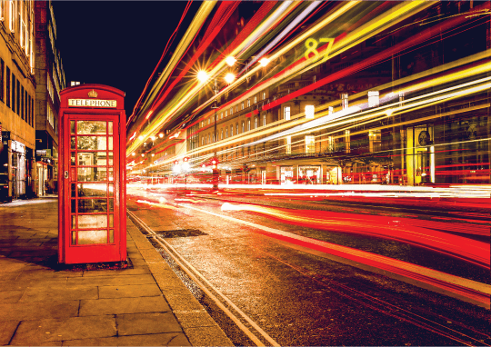Road traffic at night and a telephone box